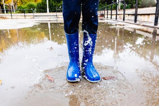 Criança espirra em uma poça de água em um parque com botas de chuva azul.