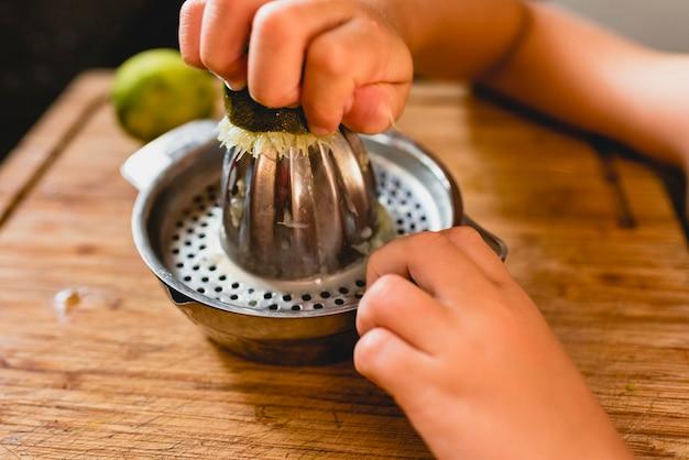 Criança espremer o suco de um limão.