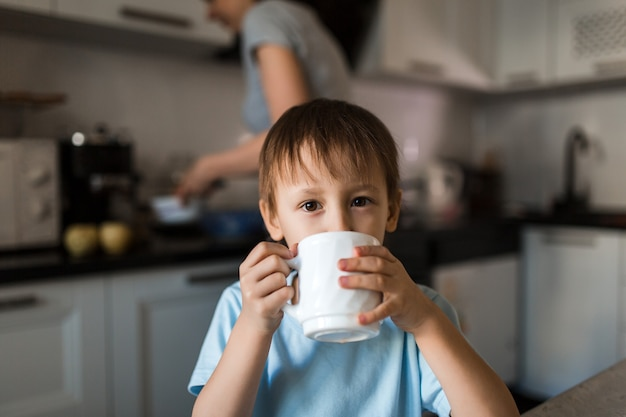 Criança está bebendo chá da caneca