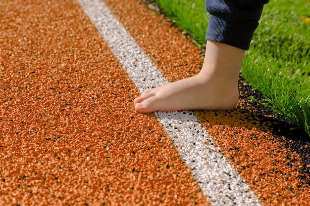 Criança está descalça na pista de atletismo laranja. principiantes no atletismo. pequeno atleta. futuro campeão.