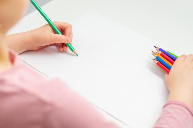 Criança está desenhando a lápis colorido