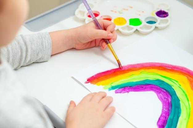 Criança está desenhando arco-íris