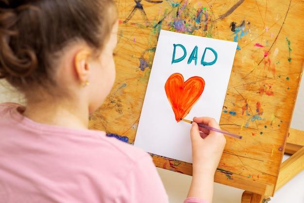 Criança está desenhando um coração vermelho com a palavra papai cartão em papel branco sobre um cavalete. conceito de feliz dia dos pais.