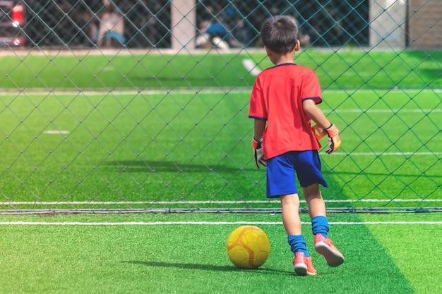 Criança está driblando a bola de futebol em um campo
