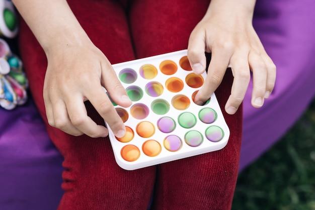 Criança está jogando um jogo popular com botões um brinquedo antiestresse jogos educativos infantis