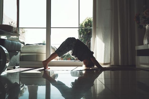 Criança está praticando ioga menino pré-escolar meditando e fazendo as posturas de ioga em casa