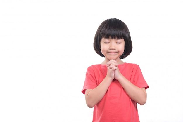 Criança está rezando, mãos cruzadas em oração