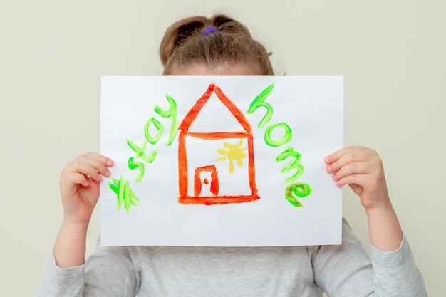 Criança está segurando a foto da casa