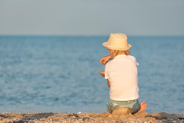 Criança está sentada na praia e brinca com areia