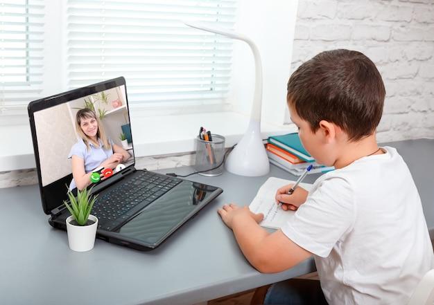Criança está tendo aulas online, vídeo chamada amplia seu professor Foto Premium
