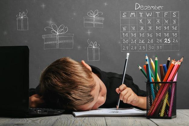 Criança estuda remotamente na escola, usando um capacete de astronauta. conceito de natal