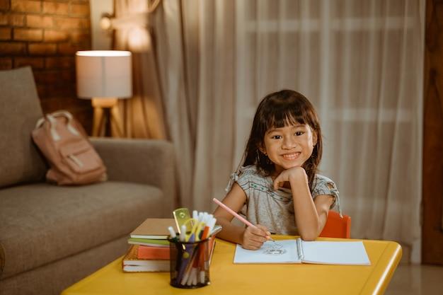 Criança estudando sozinha à noite