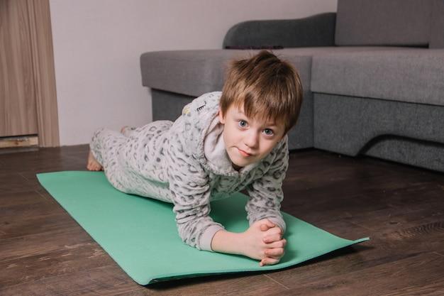 Criança européia em casa no tapete faz exercícios esportivos diferentes para fortalecer a imunidade