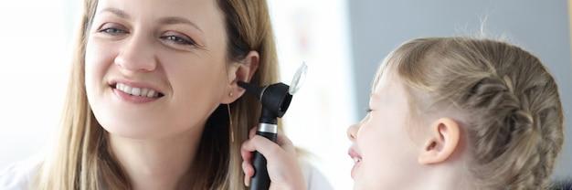 Criança examinando o ouvido do médico com otoscópio no diagnóstico clínico e no tratamento do ouvido