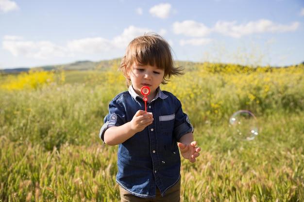 Criança faz bolhas de sabão ao ar livre