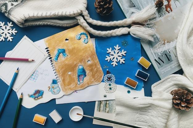 Criança faz cartões de natal (ano novo) para as férias de inverno.