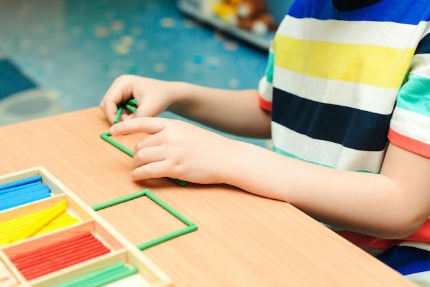 Criança faz formas geométricas de paus coloridos. educação e desenvolvimento pré-escolar. classe primária da escola. garoto na aula de matemática.