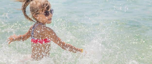 Criança faz spray no mar.