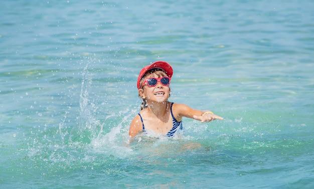 Criança faz spray no mar