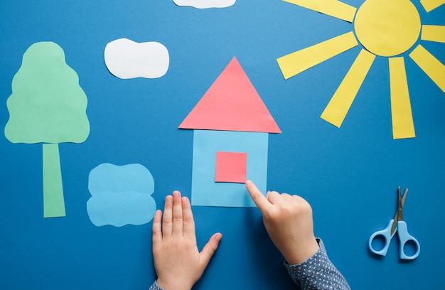 Criança faz um artesanato de papel colorido
