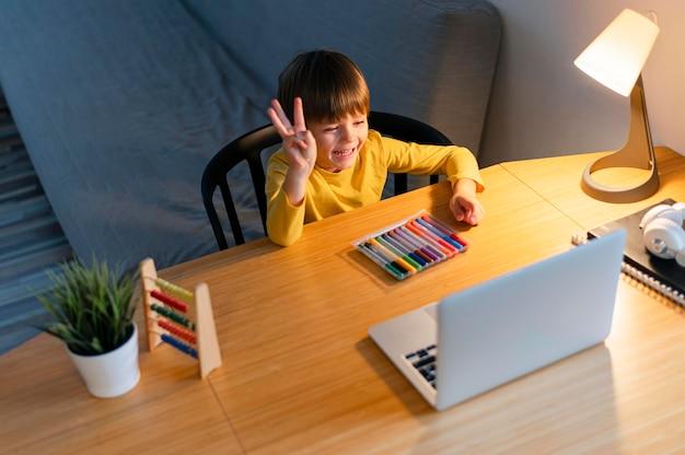 Criança fazendo cursos virtuais e levantando a mão