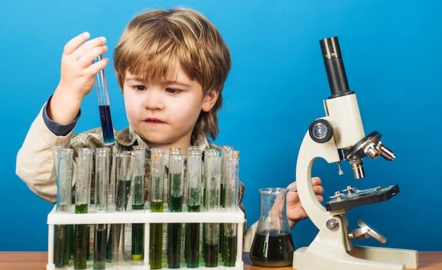 Criança fazendo experimento científico em laboratório criança com tubos de ensaio e microscópio educação