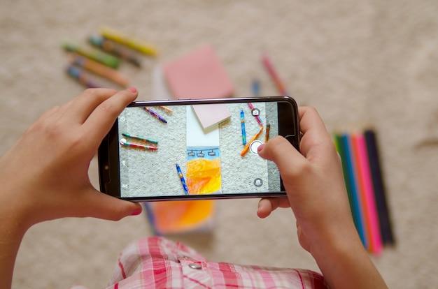 Criança fazendo foto de lápis de desenho com telefone celular. feche acima no celular creen.