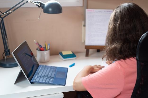 Criança fazendo lição de casa em casa com um tablet