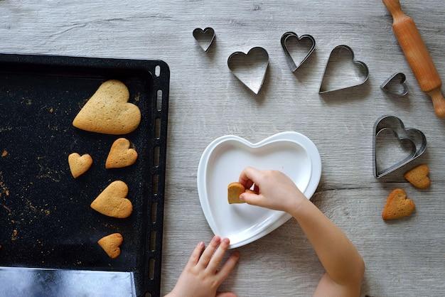Criança fazendo pão de gengibre com formato de coração.