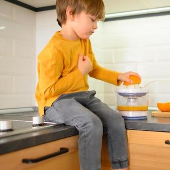 Criança fazendo um delicioso suco de laranja