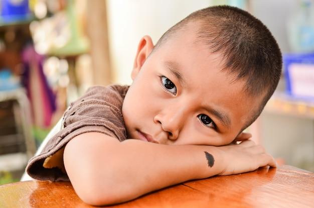 Criança fazendo uma cara triste.boy tem uma marca de nascença preta no braço