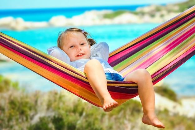 Criança feliz à beira-mar na rede