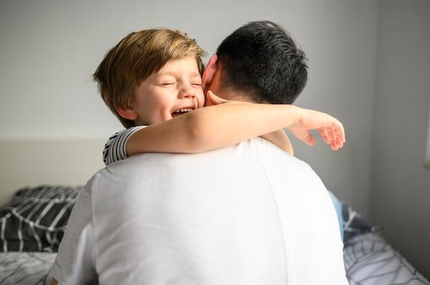 Criança feliz, abraçando seu pai