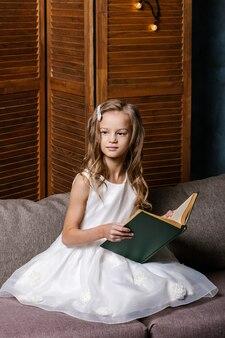 Criança feliz abrindo o livro de natal. conceito de férias de natal