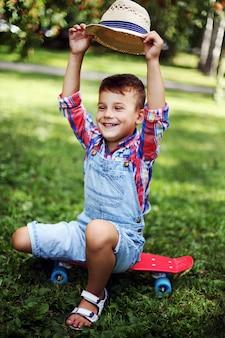 Criança feliz alegre que senta-se em um skate em um parque do verão em um dia ensolarado;