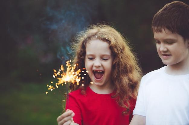 Criança feliz amigo na festa com queimando diamante na mão.