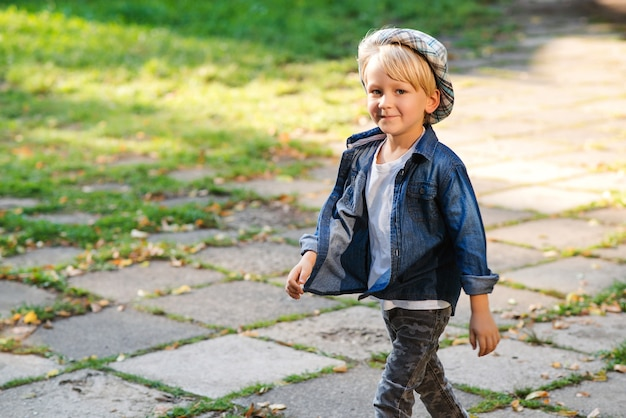 Criança feliz andando no parque. criança elegante posando ao ar livre. menino bonitinho com roupa de verão. criança com chapéu e roupas da moda. garoto se divertindo lá fora, no parque.