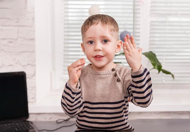 Criança feliz aprender a língua inglesa online com o laptop em casa. fique em casa