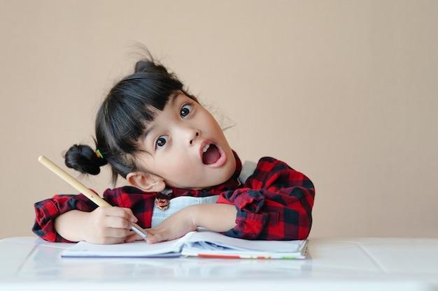 Criança feliz asiática aprendendo e apreciando a arte do desenho da pintura em aquarela em casa.