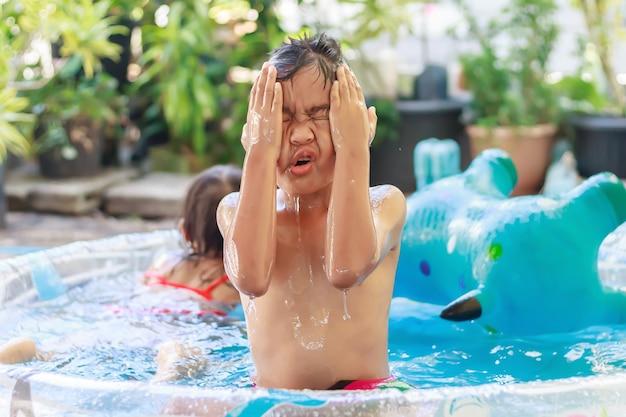 Criança feliz asiática brincando e nadando na piscina de água, temporada de verão e conceito de criança