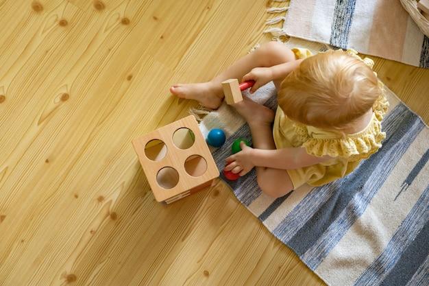 Criança feliz batendo martelo de madeira em bolas coloridas de brinquedo ecológico de desenvolvimento inicial