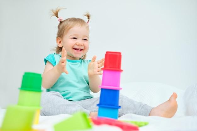 Criança feliz batendo palmas brincando com brinquedos