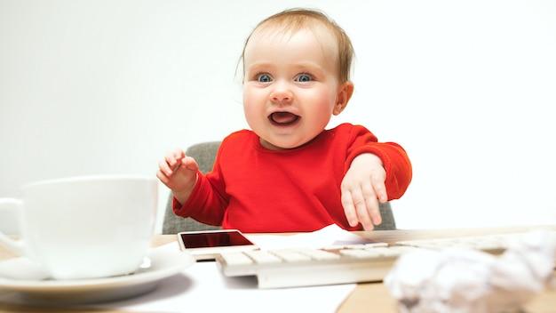 Criança feliz bebê menina criança sentada com o teclado do computador isolado