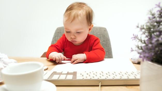 Criança feliz bebê menina sentada com o teclado do computador isolado em um branco