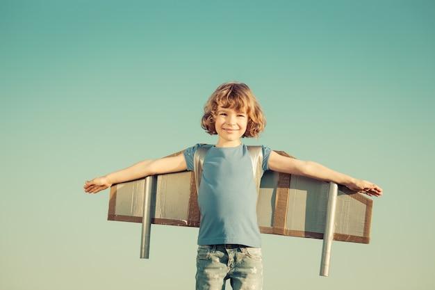 Criança feliz brincando com asas de brinquedo contra o fundo do céu de verão. retro tonificado