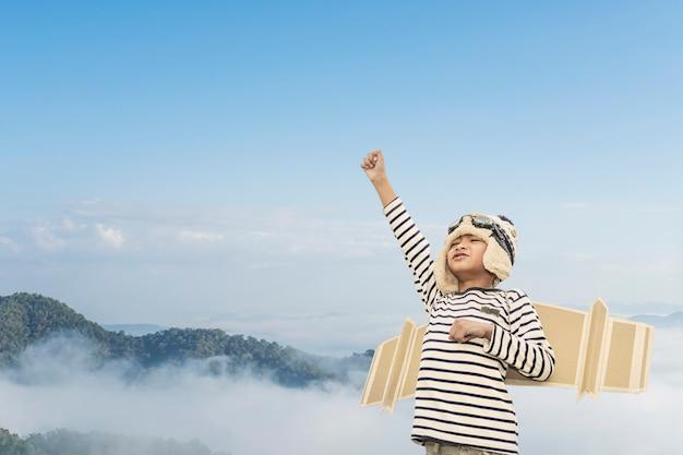 Criança feliz brincando com asas de brinquedo contra o fundo do céu de verão.