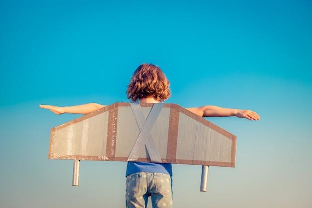 Criança feliz brincando com asas de brinquedo contra o fundo do céu de verão