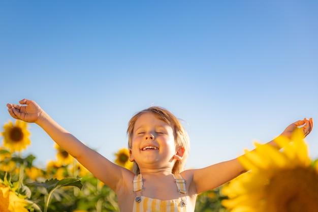 Criança feliz brincando com girassol ao ar livre