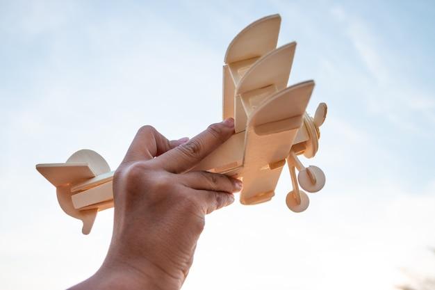 Criança feliz, brincando com o avião de brinquedo de madeira contra o céu do sol