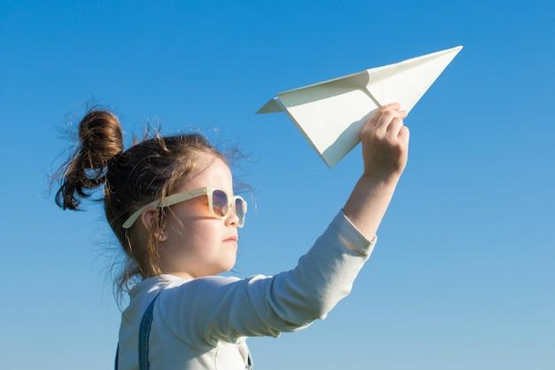 Criança feliz, brincando com o avião de papel